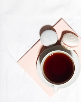 Box of macaroons with cup of tea
