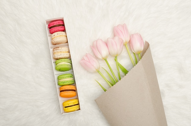Box of multicolored macaroons and pink tulips on white fur, top view