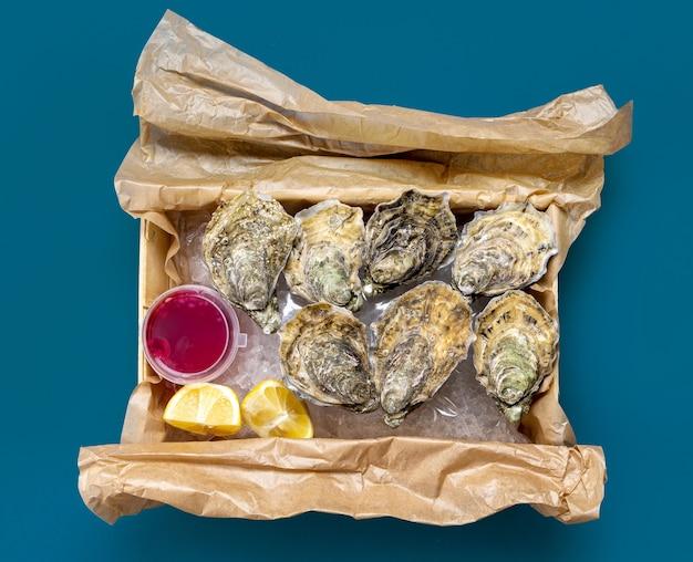 Коробка открытых свежих устриц, лимонного и уксусного лукового соуса на синем фоне, вид сверху