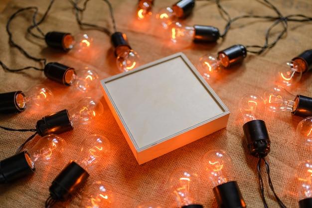 Ящик из фанеры в окружении ретро-гирлянды с лампами эдисона