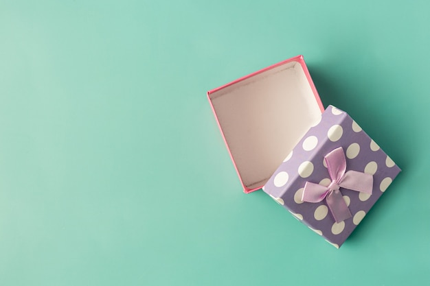 Коробка подарка с бантом на светло-зеленом фоне