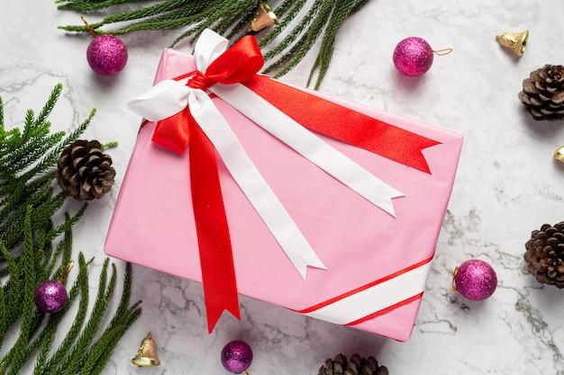 大理石の背景にクリスマスの飾りとプレゼントの箱