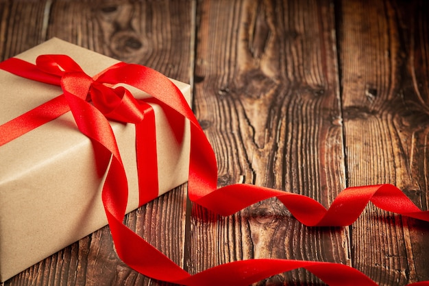 나무 바탕에 빨간 리본 활과 선물 상자