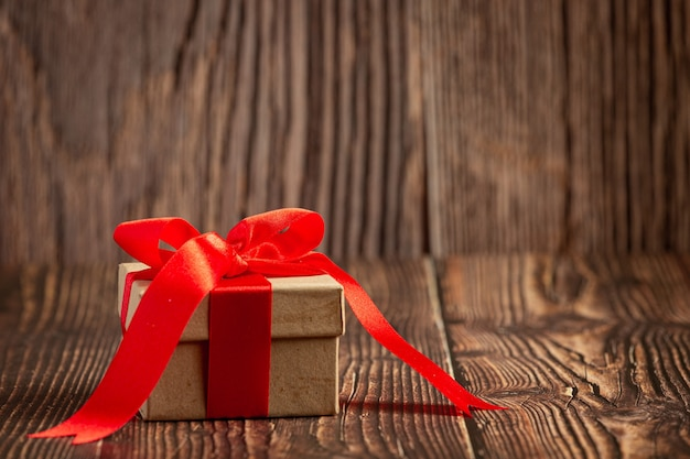 木製の背景に赤いリボンの弓とプレゼントの箱
