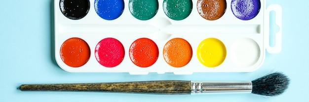 Коробка акварельных красок и кистей для рисования на синем фоне. знамя
