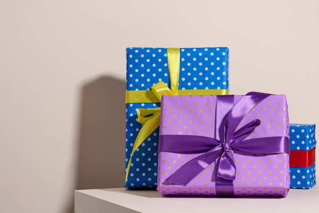Box packed in festive purple paper and tied with silk ribbon on a beige background, birthday gift, surprise