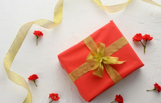 Box packed in holiday red paper and tied with a silk ribbon on a background, birthday gift, surprise