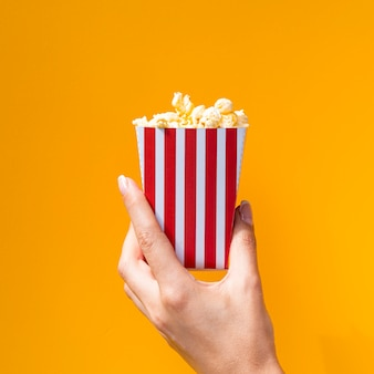 Box of popcorn on orange background