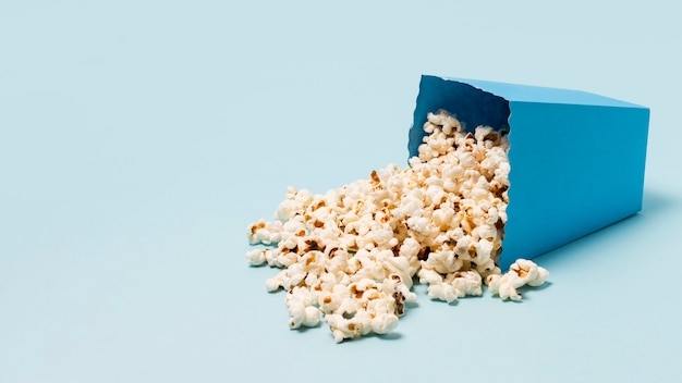 Box of popcorn spilled on blue background