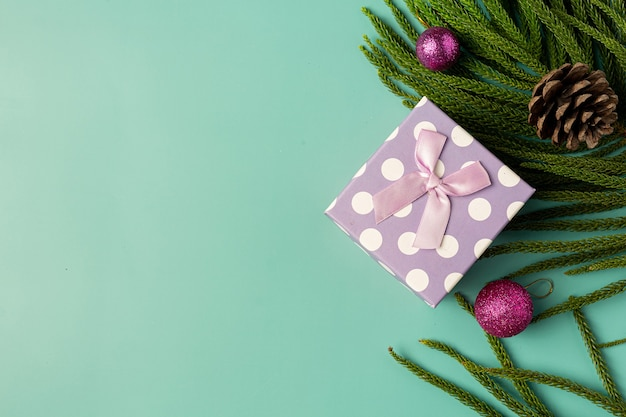 Box of present with bow on light green background