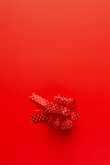 Box of present with red ribbon bow on red background