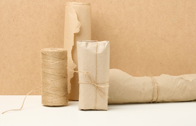 Box, roll of brown kraft paper and reel with brown rope on white table, packing material, zero waste