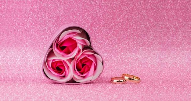 バレンタインデーのボケ味と光沢のある背景にバラの金の結婚指輪とボックスサプライズギフトピンクのハート