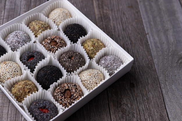 Box of vegan sweets energy balls on wooden table