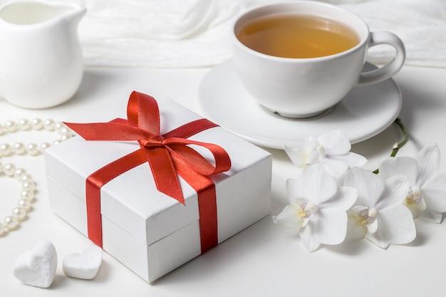 ギフトと白い背景の上の白い蘭の箱。