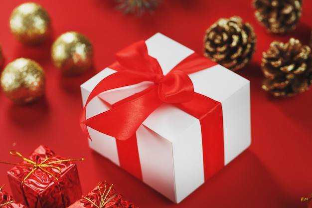Коробка с красным бантом вокруг елочных игрушек на красном фоне