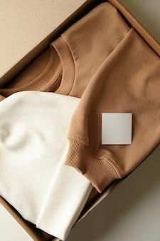 Коробка с шапкой и толстовкой на белой поверхности
