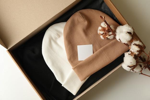 Коробка с шапочками и хлопком на белой поверхности