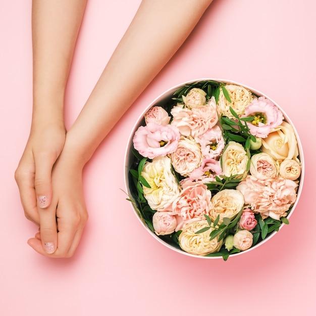 コピースペースと黒の背景に女性の手の横に美しい花のボックス Premium写真
