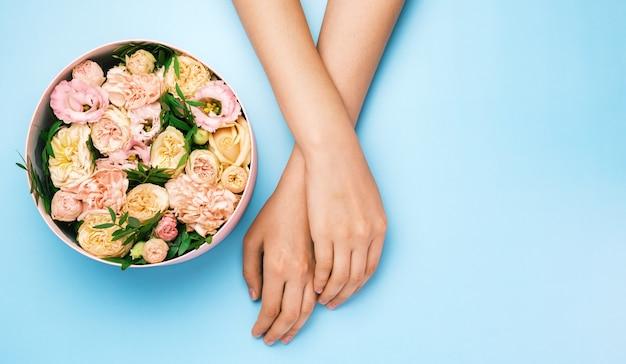 Коробка с красивыми цветами рядом с женскими руками на синем фоне с копией пространства. красота