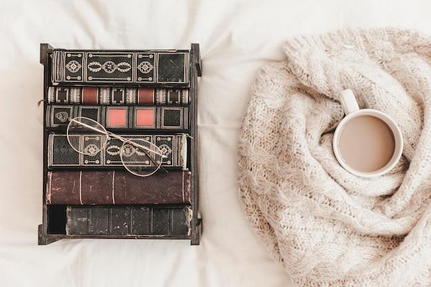 Коробка с книгами возле горячего напитка в плед