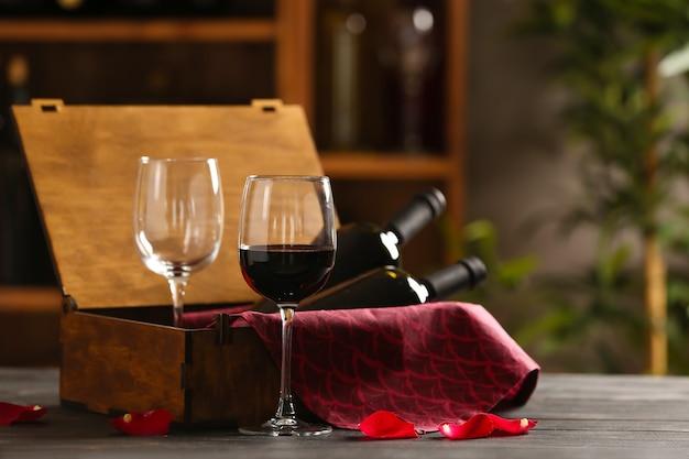 Коробка с бутылками вина и бокалами на столе