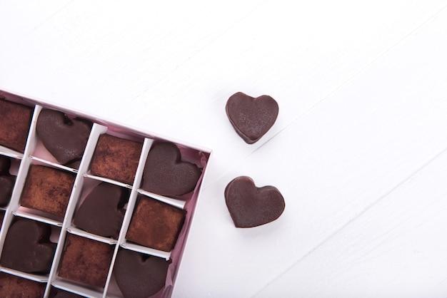 Коробка с шоколадными конфетами в форме сердца на белом фоне. концепция дня святого валентина. скопируйте пространство.