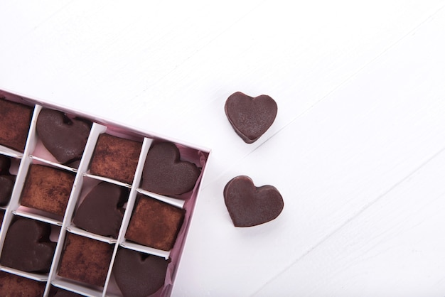 Box with chocolate heart shaped sweets on white background. valentine day concept. copy space.