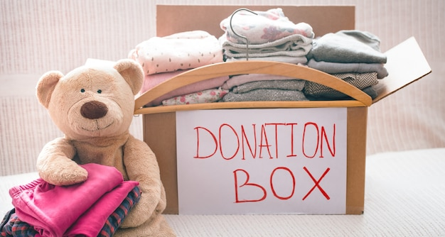 Box with clothes for charity and teddy bear with hanger