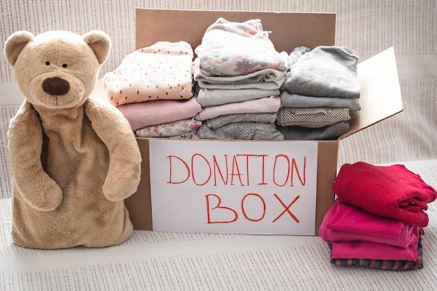 Коробка с одеждой для благотворительности и плюшевого мишки