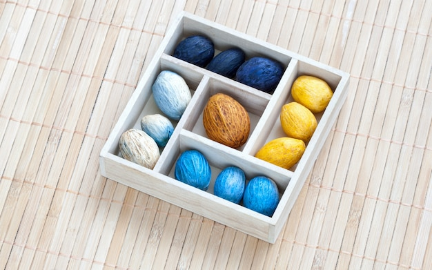Box with colored nuts on a bamboo napkin