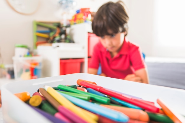 Box with coloring pencils and kid