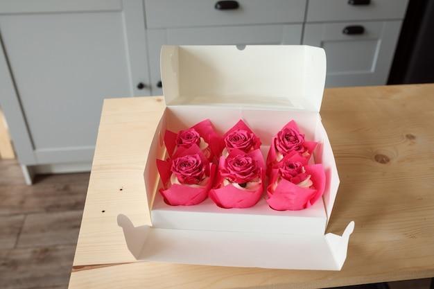 テーブルの上のバラのつぼみで飾られたクリーミーなカップケーキの箱、デザートの配達のコンセプト。