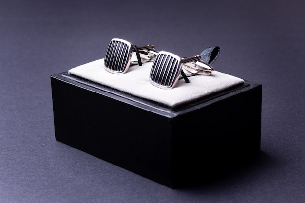 Box with cufflinks for man suit on black