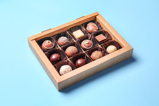 Коробка с вкусными шоколадными конфетами на цветной поверхности