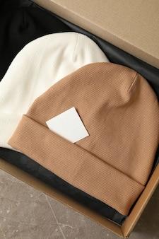 Коробка с разными шапочками на сером столе