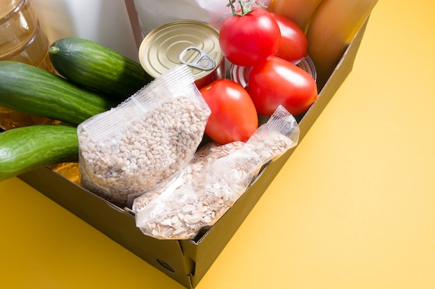 Box with essential products on yellow background, donation or delivery concept