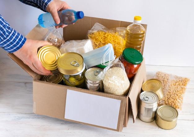 食料品の入った箱。バター、缶詰、シリアル、パスタが入った段ボール箱。予約します。寄付。