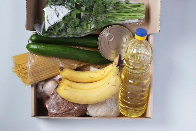 Коробка с продуктами питания на голубом. рис, гречка, макаронные изделия, консервы, бананы, огурцы, яйца, масло растительное. доставка еды, пожертвование, вид сверху
