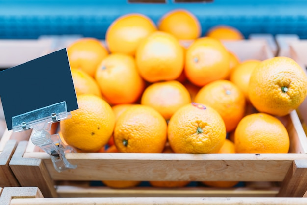 食料品店のスタンドに新鮮なオレンジが入った箱。市場の果物の品揃え