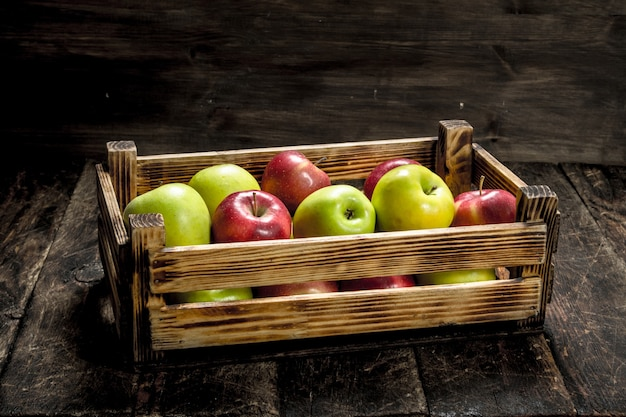 신선한 빨강 및 녹색 사과 상자. 나무 배경.
