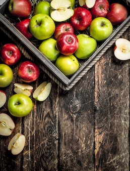 新鮮な赤と緑のリンゴが入った箱。木製の背景に。