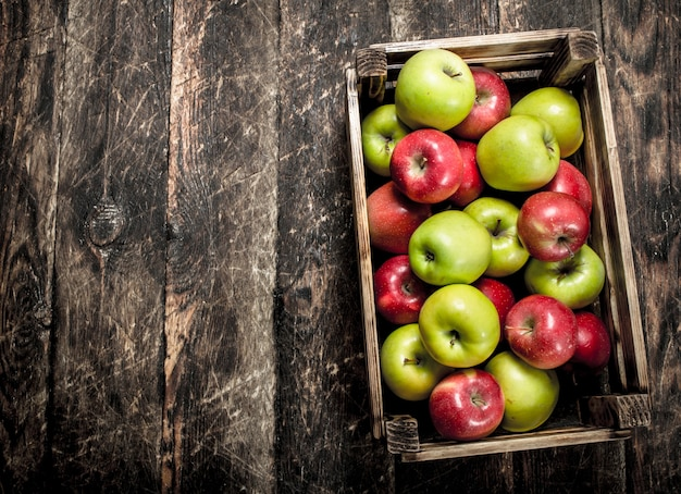 Box with fresh red and green apples on wooden table.