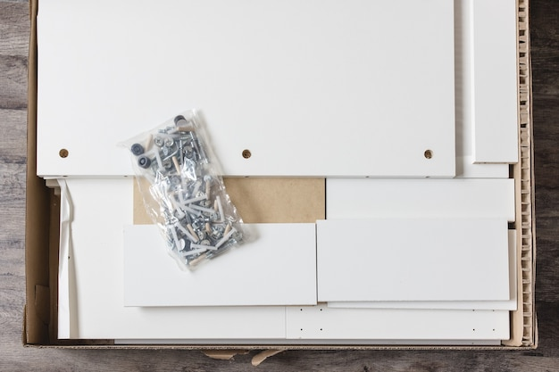 Box with furniture assembly parts on the floor