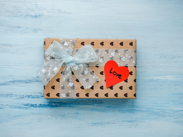 Box with a gift, tied with a ribbon, note with sweet words
