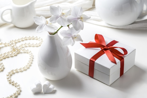 Box with a gift and a white orchid on a white background.