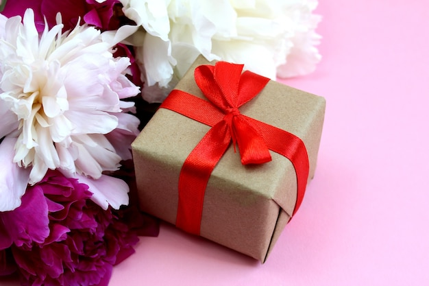 A box with a gift with a bow stands against a background of bright peony flowers on a pink background