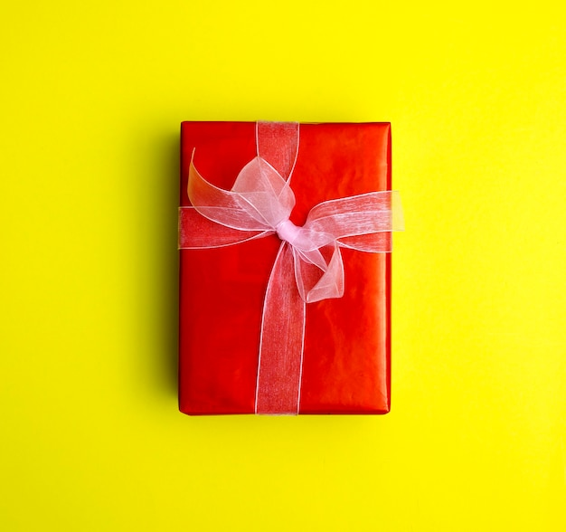 Box with gifts and surprises on a yellow