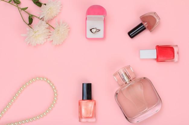 ピンクの背景に金の指輪、ビーズ、香水のボトル、マニキュアと花のボトルが入った箱。女性の化粧品とアクセサリー。上面図。