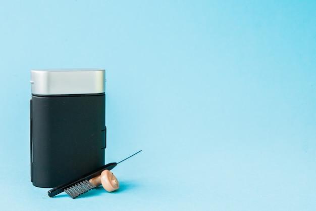 Коробка со слуховым аппаратом и аксессуарами на цветной стене. концепция медицины, фармации и здравоохранения. копировать пространство пустое место для текста или логотипа